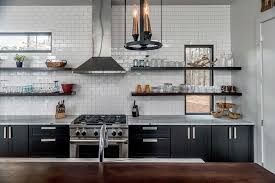 view full size contemporary kitchen features black base cabinets paired with marble countertops and a white subway tiled backsplash