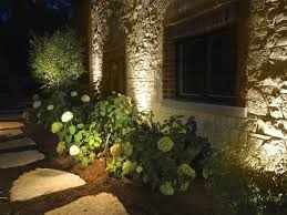 Image Hgtv 22 Landscape Lighting Ideas This Exterior Is Also Uplit To Highlight The Stonework And Path Light In Front Spreads Its Beam Over Bank Of Hydrangeas Pinterest 22 Landscape Lighting Ideas Landscaping Landscape Lighting