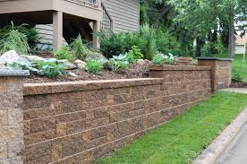 stunning retaining wall design beautified with refreshing green plants and high trees around it
