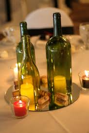 centerpiece: 3 wine bottles w/ flowers on mirror w/ corks around