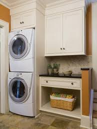 Contemporary laundry room idea in New York with orange walls and a stacked  washer/dryer