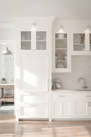 white fridge in kitchen. white shaker kitchen cabinets with a custom matching fridge in
