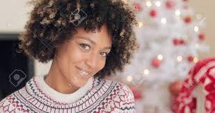 Jolie Jeune Femme Africaine Avec Une Coiffure Afro Souriant à La Caméra Alors Quelle Pose Dans Son Salon Devant Un Arbre De Noël En Gros Plan