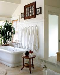 Bathrooms:Attic Bathroom With White Bathtub Near Woode Side Table And Towel  Display Arrangement On
