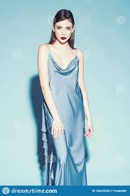 on strict confident face in long blue dress light blue background lady with red lips looking at camera woman fashion model with stylish makeup and