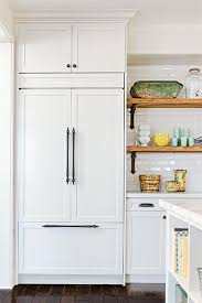 custom panels help this builtin refrigerator melt into the surrounding allwhite kitchen built in p17