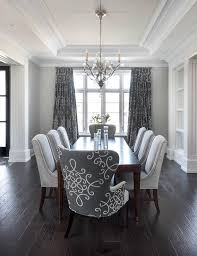 gray dining room features a tray ceiling accented with a satin nickel and glass chandelier illuminating a dark stained curved dining table lined with dove