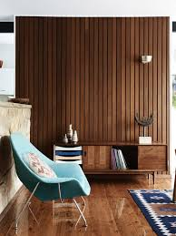 a mid century modern space with a wood plank wall matching floor and furniture