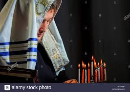 Prayer For Lighting The Menorah Candles A Jewish Man In Prayer And Lighting Candles In A Menorah