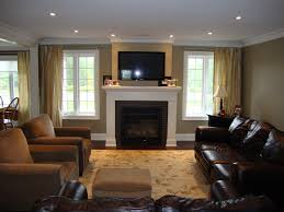 Great room with windows flanking fireplace, furniture placement, low  ceiling, pot light placement