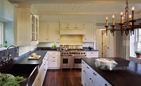 off white kitchen kitchen farmhouse with black countertop dark wood floor dark wood floor