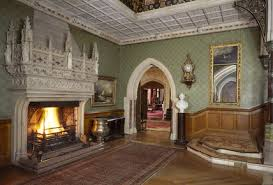 view of the main hall at tyntesfield with huge stone carved fireplace and a pointed arched doorway to ante room drawing beyond t4 fireplace