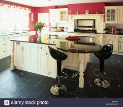 Kitchen With Slate Floor Black Bombo Stools At Curved Breakfast Bar In Red Kitchen With