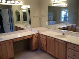 interior brown wooden bathroom vanity with white top and large mirror on white wall