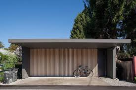 the light wood vertical slats on this garage door make for a modern statement and a unique door