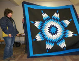 Untitled & Jodi Bourue, guest, shows a Traditional Native American Star quilt;strip  pieced and Adamdwight.com