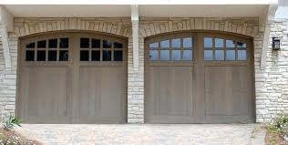 garage door facade two car garage features natural wood arched doors with upper panel windows nestled