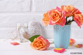 fresh orange roses in blue cup and decorative heart on white wooden background against brick wall
