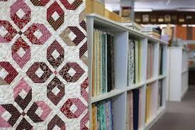 Quilts & Other Notions reopens under new owner   Creston News ... & A quilt hangs next to a variety of fabrics at Quilts & Other Notions in  Creston Adamdwight.com