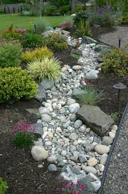 Create a beautiful and low maintenance garden incorporating river rock;  landscaping with a dry stream