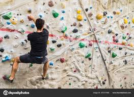 a man practicing rock climbing on artificial wall indoors active lifestyle and bouldering concept photo by ihorga on rock climbing artificial wall with man practicing rock climbing artificial wall indoors active
