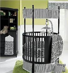 Black Round Crib With Drawers And Green Rug And White Curtains