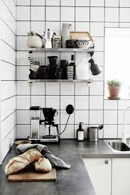 white matte square tile backsplash black grout stainless steel floating shelves coffee maker cups bowls potted plant breads concrete countertop white