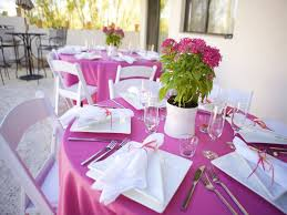 pink wedding party decorations with large round tables and white wooden folding chairs also small flower tables centerpiece