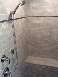 Walk-in shower with 3x6 grey subway tile, metal pencil liner accent, bench