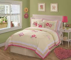 yellow and pink fabric fl bedding on white wooden bed connected by small pink table lamp on bedside table