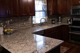 cherry cabinets with brushed nickel hardware provide a nice contrast to the light backsplash and countertops the sink is an under mount composite granite