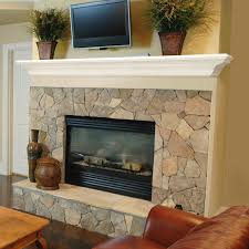 interior beige stone fireplace with white wooden mantel shelf and rectangle black metal firebox
