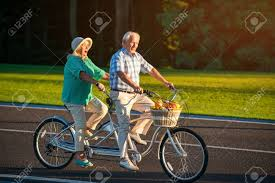 senior couple on tandem bike bicycle with fruit basket lovers