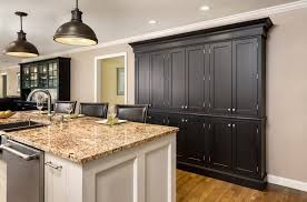 black wall of pantry cabinets in and white island built of shaker inset cabinets with nickel
