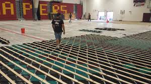 a worker walks across the recycled plastic that will make up the lower layer of cape elizabeth high school s new gym flooring part of the maple