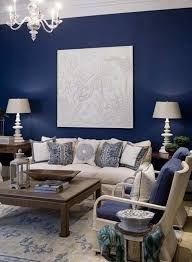 navy blue wall color with white wall hanging for traditional living room design with crystal chandelier