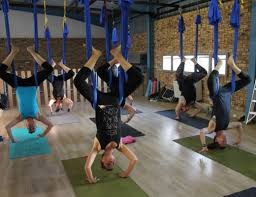 the class prepares to move into a chandelier yoga position
