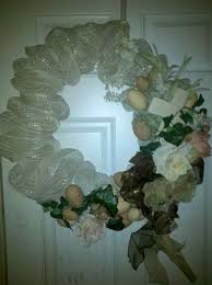 easter wreath made out of a hanger with hand painted eggs ribbon and flowers