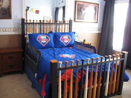 bed with baseball bat frame having blue comforter also blue pillow case on cream carpet with with football toddler bed set