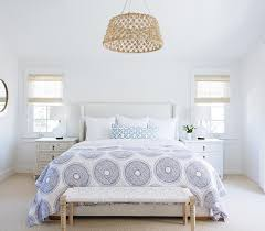 gorgeous bright bedroom features a jute rope drum pendant hanging over a white wingback bed dressed in a blue medallion quilt john robshaw lapis quilt
