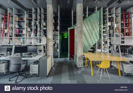loft style office. Loft Style Office With Concrete Columns And A Gray Carpet. There Is Metal Green-red Stairway Tunnel-structure, Yellow Table Chairs, Workpl I