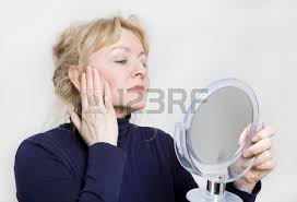 woman holding hand mirror. holding mirror: an older woman looking in a hand mirror on her face
