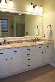 white bathroom cabinets with bronze hardware. bathroom - repainted our oak cabinets with cream colored paint, added oil-rubbed bronze hardware, a granite countertop, new faucets and lighting, white hardware i