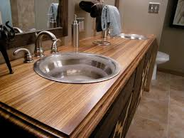 wooden inexpensive bathroom vanity options with two round stainless steel sinks under framed mirrors