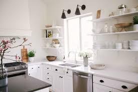clean white kitchen cabinets with black hardware in a minimalist kitchen