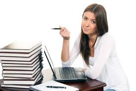 major benefits of writing services online   it is cool brunette business woman sitting in an office working on her laptop computer pc with a pen