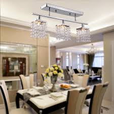 brushed nickel circolo linear chandelier for modern dining room design with white parson chairs and table