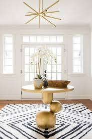 modern gold foyer table with black and white rug