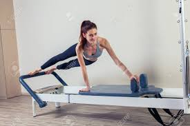pilates reformer workout exercises woman brunette at gym indoor stock photo 47852778