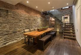dining room with with free standing wooden dining table and chairs with exposed brick wall